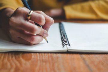 Hand writing with pencil in spiral bound notebook